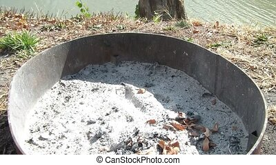 Sticks Thrown into Firepit with Ashes - Sticks are thrown...