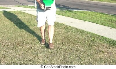 Spreading Lawn Fertilizer in Sunlight - Man spreads lawn...