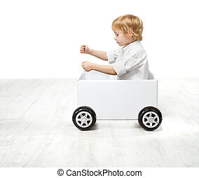 Child driving box car. Creativity and innovation concept