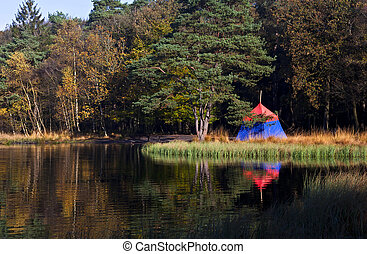 old fashioned tent in forest close to lake