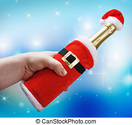 hand holding a champagne bottle in a Christmas decoration santa clothes on a blue background