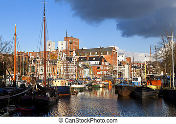sunny canal in Groningen with many river boats befire storm