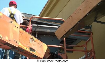 Two Workers on Lift - Two workers on lift apply materials to...