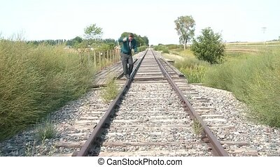 Walking Fine Line on Railroad Tracks - Businessman walks a...