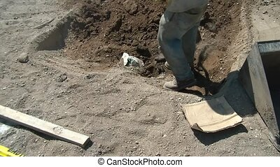 Worker Digging Hole in Dirt - Construction worker digging a...