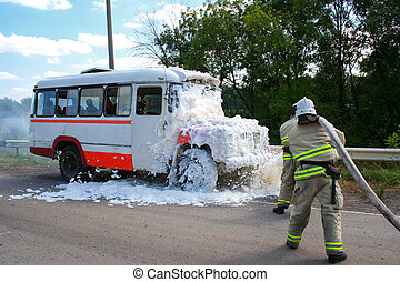 Firefighters extinguish a fire in a burning bus standing at...