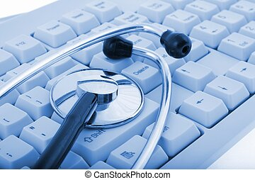 A stethoscope on a computer keyboard on blue tone