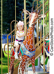 Girl riding on a carousel - The image of a girl riding on a...