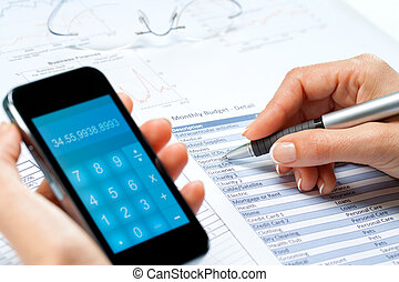 female hands calculating budget with smart phone - macro...