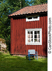 Empty chair in sunlight alongside a timber house - Empty...