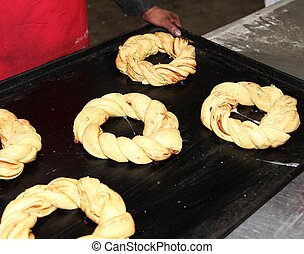 Baker in a industrial bakery with baking tray