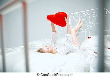 Girl lying on the bed with a red heart