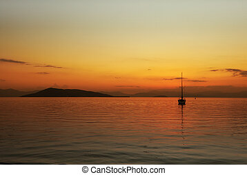 End of the day - Sunset over Angistri on the left and the...