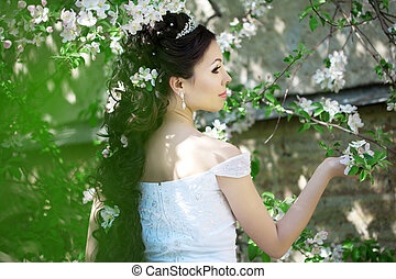 Beautiful bride in a blossoming garden - The image of a...