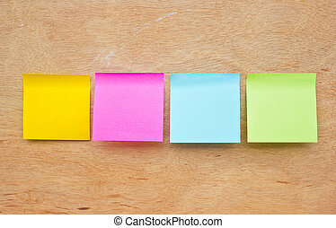 Four colorful sticky notes on wooden board.