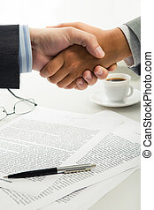 Handshake over workplace - Image of business handshake over...