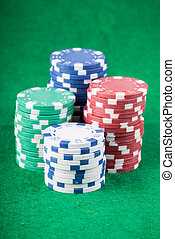 Poker chips on green playing table