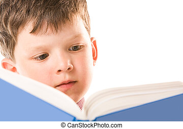 Reading the book - Image of young boy reading the book on a...