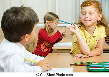 During lesson - Photo of cute schoolgirl with blue pencil in...