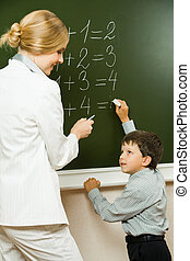 Helping - Photo of elementary student doing sums on...