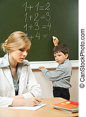Education - Image of schoolboy writing numbers on the...