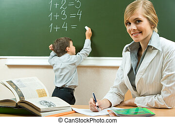 Teacher - Portrait of pretty teacher sitting at the table on...