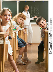 In the classroom - Image of curious schoolchildren sitting...