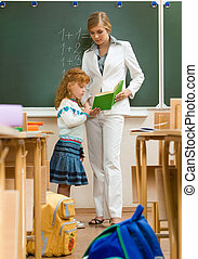 Studying - Photo of schoolgirl and teacher reading book...
