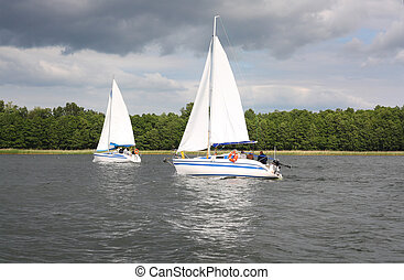 white yachts sail in the lake , Mazury, Poland