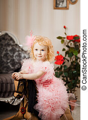 ?hild in a pink dress on a toy horse - A little sweet girl,...