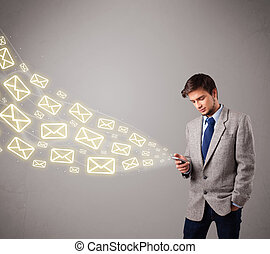 attractive young man holding a phone with message icons