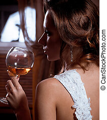 Beautiful bride in dress with wine glass