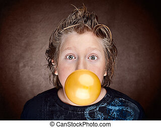 Boy blowing balloon - Humorous photo of young boy blowing up...