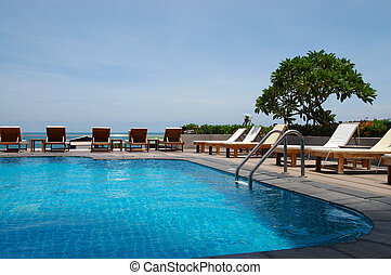 Poolside#9 - White trestle-beds near the resort\\\'s pool