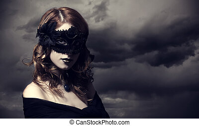 Enchantress at storm sky background. - Enchantress in mask...