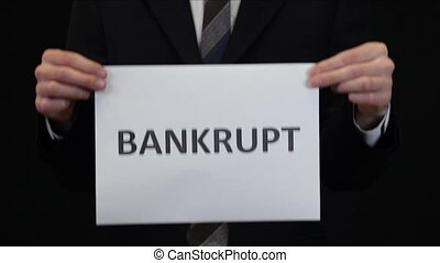 Bankrupt Businessman - Business man holding sign BANKRUPT in...
