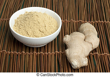 Powdered ginger in a bowl and whole ginger on wooden base