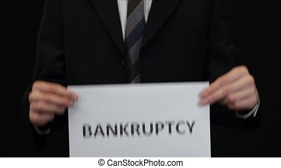 Businessman Showing Bankruptcy Sign - Business man holding...