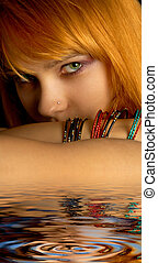 look - dark portrait of lovely redhead in water