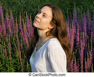 Enjoying nature - young woman surrounded by wild flowers