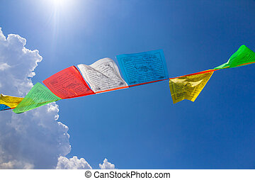 Few buddhist tibetan prayer flags against blue sky with a...
