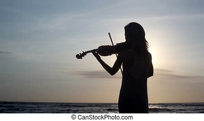 Romantic scene - Silhouette of violinist playing on violin...