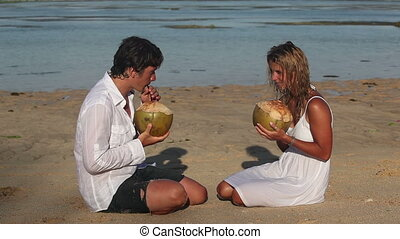 Love dating - Attractive couple drinking coconuts and...