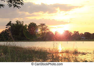 Sunset at coast of the lake with small village
