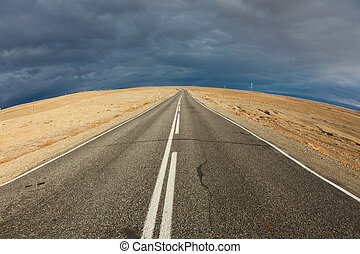 An empty desert road with dark and foreboding storm clouds...