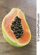 Halved papaya on wooden surface