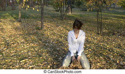 A young woman throws yellow leaves