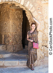 Woman in long light dress standing near ancient arch in...