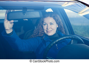 Pretty woman in car preparing to driving correcting back...