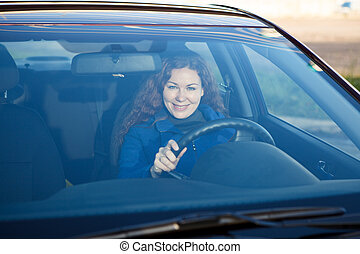 Attractive driver inside of car smiling through the...